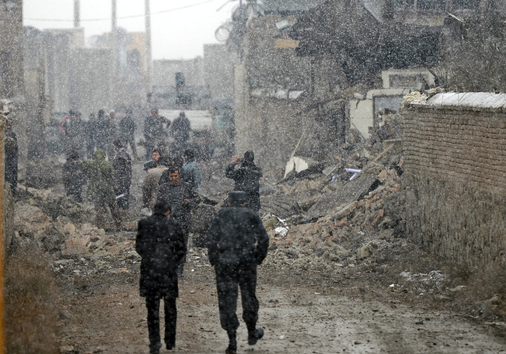 Description of . Afghanistan policemen and security forces walk at the site of an explosion in Kabul on December 17, 2012. A car bomb exploded at a compound owned by a US-based construction company under contract to the Afghan army, killing at least one person and wounding 15, police said. Five foreigners including those from the US and South Africa were among the wounded, a security source at the company told AFP. MASSOUD HOSSAINI/AFP/Getty Images