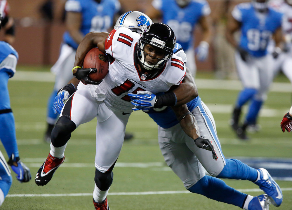 Description of . Atlanta Falcons wide receiver Julio Jones (11) tries breaking free from Detroit Lions middle linebacker Stephen Tulloch during the first quarter of an NFL football game at Ford Field in Detroit, Saturday, Dec. 22, 2012. (AP Photo/Duane Burleson)