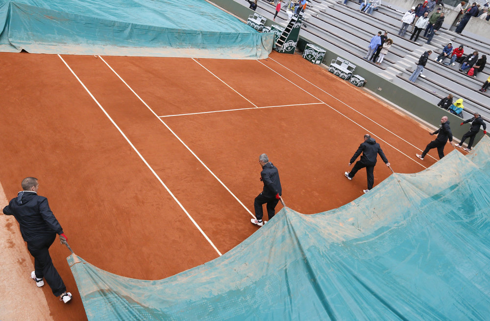 . Employees cover a court as rain falls at the Roland Garros stadium during the third day of the French tennis Open in Paris on May 28, 2013.   KENZO TRIBOUILLARD/AFP/Getty Images