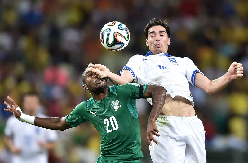 . Greece\'s midfielder Lazaros Christodoulopoulos (R) challenges Ivory Coast\'s midfielder Geoffroy Serey Die during the Group C football match between Greece and Ivory Coast at the Castelao Stadium in Fortaleza during the 2014 FIFA World Cup on June 24, 2014. (ARIS MESSINIS/AFP/Getty Images)