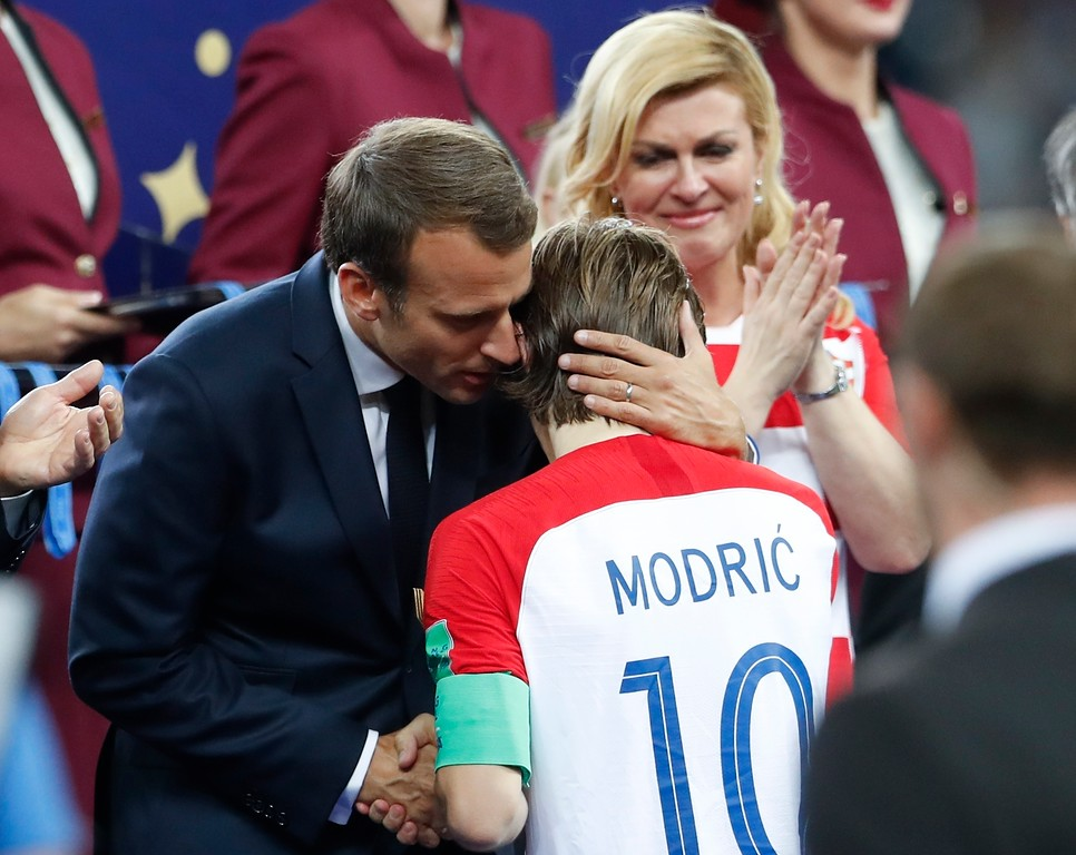 . French President Emmanuel Macron is flanked by Croatian President Kolinda Grabar-Kitarovic as he hugs Croatia\'s Luka Modric at the end of the final match between France and Croatia at the 2018 soccer World Cup in the Luzhniki Stadium in Moscow, Russia, Sunday, July 15, 2018. France won 4-2. (AP Photo/Petr David Josek)