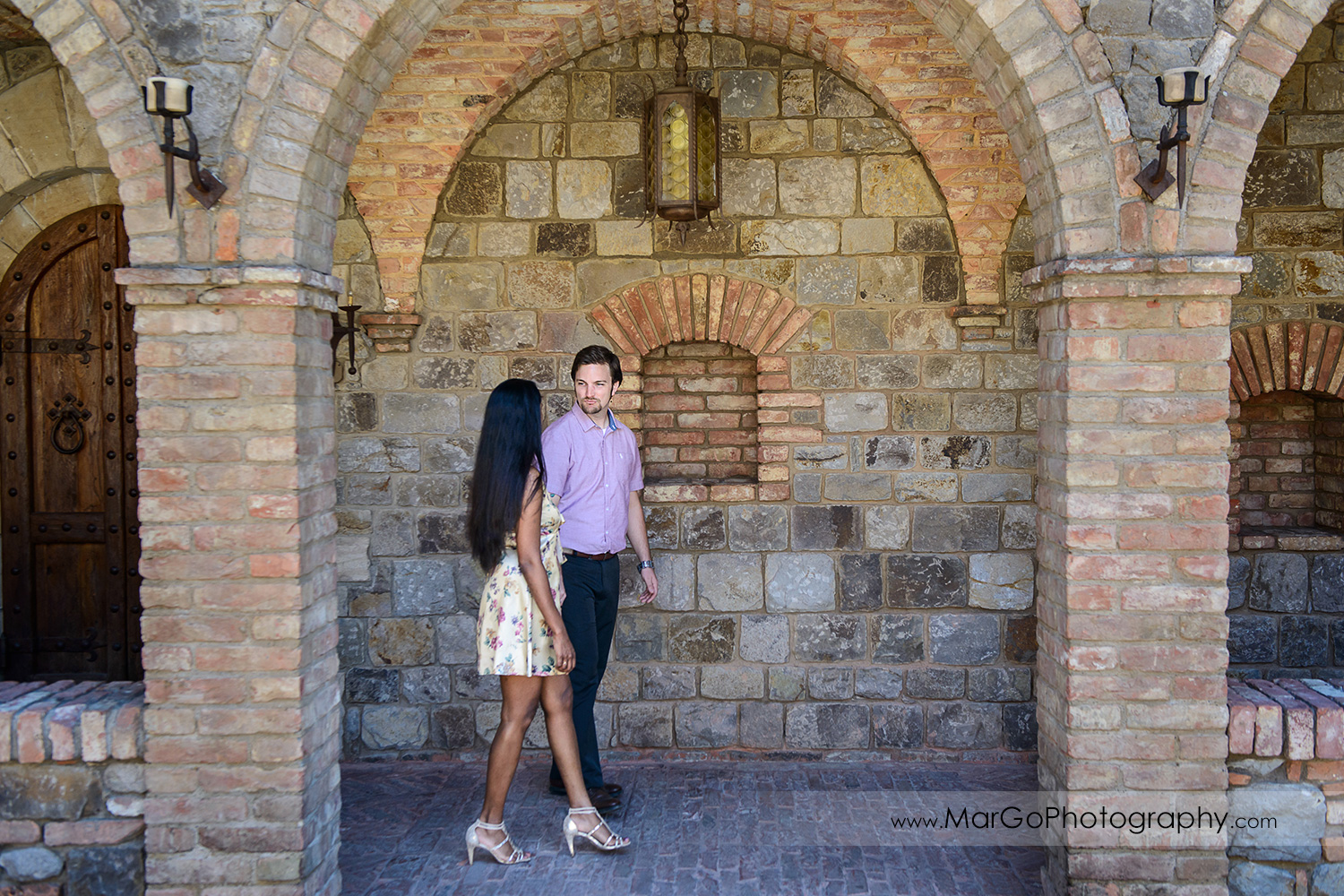 man in pink shirt and Indian woman in flower dress holding hands and walking on brick cloisters during engagement session at Castello di Amorosa in Calistoga