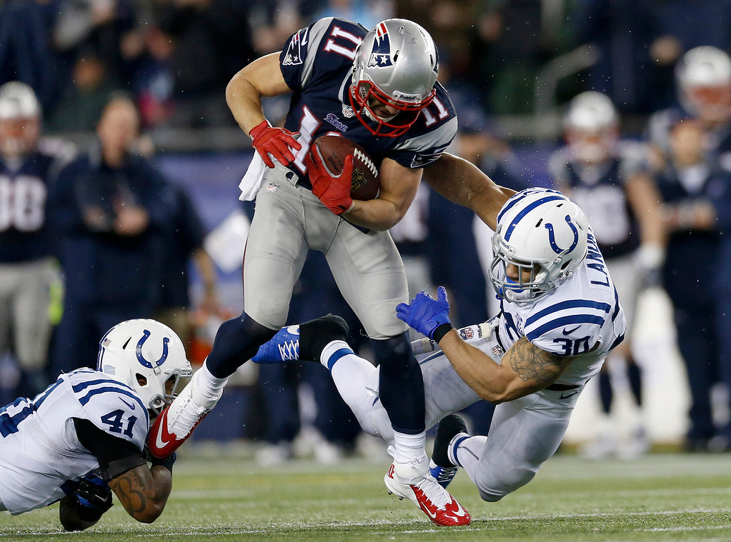 . New England Patriots wide receiver Julian Edelman (11) runs between Indianapolis Colts safeties Antoine Bethea (41) and LaRon Landry (30) during the first half of an AFC divisional NFL playoff football game in Foxborough, Mass., Saturday, Jan. 11, 2014. (AP Photo/Michael Dwyer)