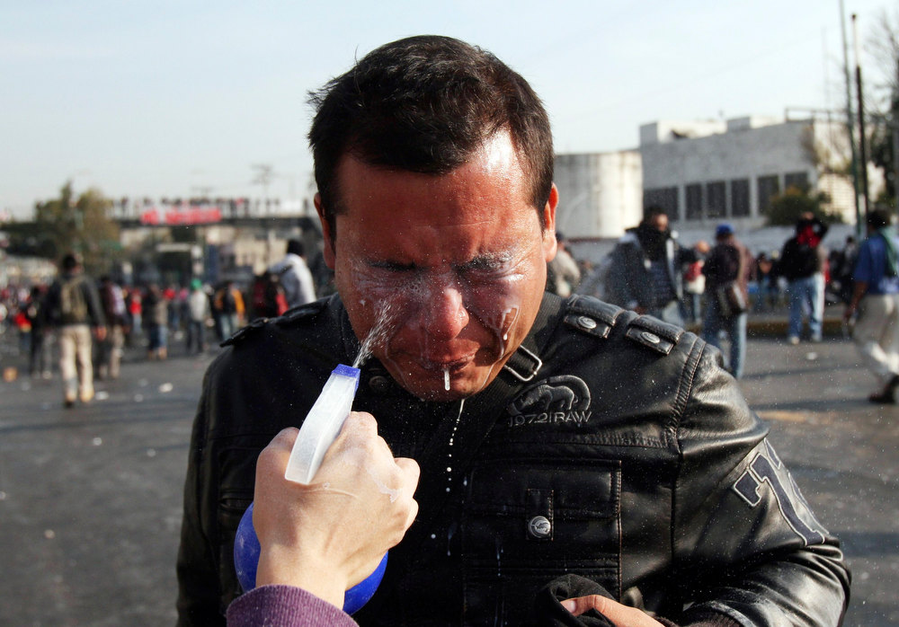 . A protester has his eyes washed after coming into contact with tear gas fired during protests against Mexico\'s new President Enrique Pena Nieto outside congress in Mexico City December 1, 2012. Pena Nieto took over as Mexican president on Saturday, offering a shot at redemption for the party that shaped modern Mexico if he can bring about an end to years of violence and economic underperformance. REUTERS/Ginnette Riquelme