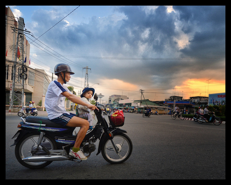 Vietnam man and boy riding a scooter.