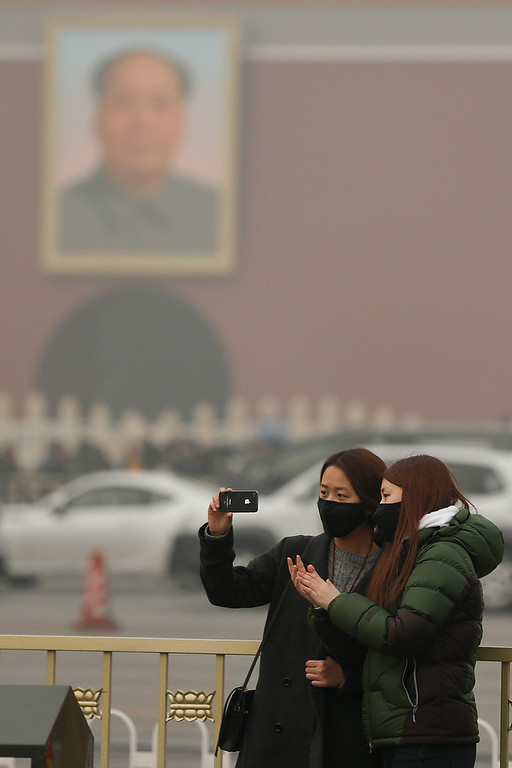 . Chinese tourist wearing the masks at the Tiananmen Square during severe pollution on February 25, 2014 in Beijing, China. The air pollution has caused an increase in the number of people seeking hospital treatment for respiratory problems and the public are asked to avoid outdoor activities.  (Photo by Lintao Zhang/Getty Images)