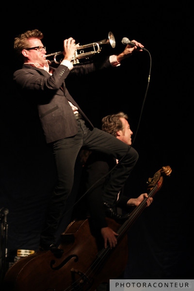 The Dusty 45s finishing up Wanda Jackson's set in style, with Billy Joe Huels blowing his trumpet while standing on top of Jeff Gray's stand-up bass.  (Photo by Benjamin Padgett)