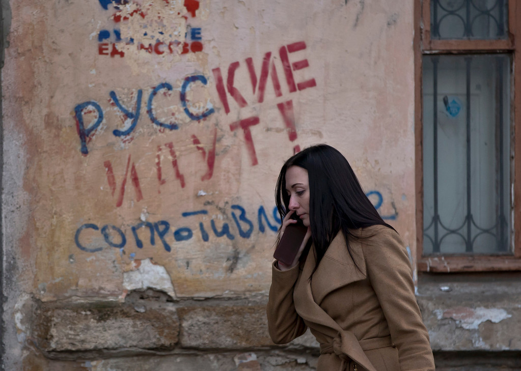 """. In this Friday, March 7, 2014 file photo, a woman passes by a graffiti that reads \""""The Russians are coming - Resistance\"""" in Simferopol, Ukraine. For the ethnic Ukrainians and Tatars who are the minority in the strategic peninsula, it is fear that dominates days before Crimea votes in a referendum on joining Russia. (AP Photo/Vadim Ghirda, File)"""