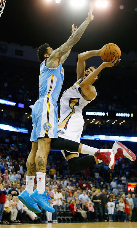 . New Orleans Pelicans power forward Anthony Davis (23) shoots around Denver Nuggets small forward Wilson Chandler (21) in overtime in an NBA basketball game in New Orleans, Sunday, March 9, 2014. The Pelicans defeated the Nuggets 111-107. (AP Photo/Bill Haber)
