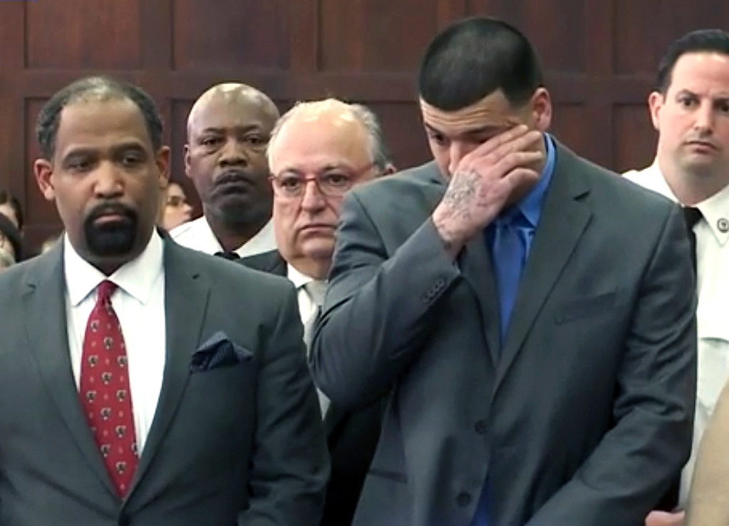 . In this still image from video, Aaron Hernandez, right, listens beside defense attorney Ronald Sullivan, Friday, April 14, 2017, in court in Boston, as he is pronounced not guilty of murder in the 2012 shootings of two men in a drive-by shooting in Boston. (WHDH-TV via AP, Pool)