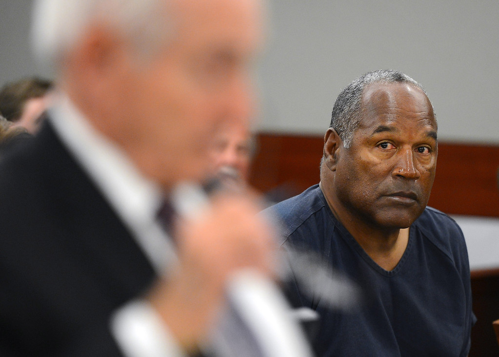 . O.J. Simpson looks at Chief Deputy Clark County District Attorney H. Leon Simon speaks during an evidentiary hearing for Simpson in Clark County District Court on Tuesday, May 14, 2013 in Las Vegas.  The hearing is aimed at proving Simpson\'s trial lawyer, Yale Galanter, had conflicted interests and shouldn\'t have handled Simpson\'s case. Simpson is serving nine to 33 years in prison for his 2008 conviction in the armed robbery of two sports memorabilia dealers in a Las Vegas hotel room. (AP Photo/Ethan Miller, Pool)