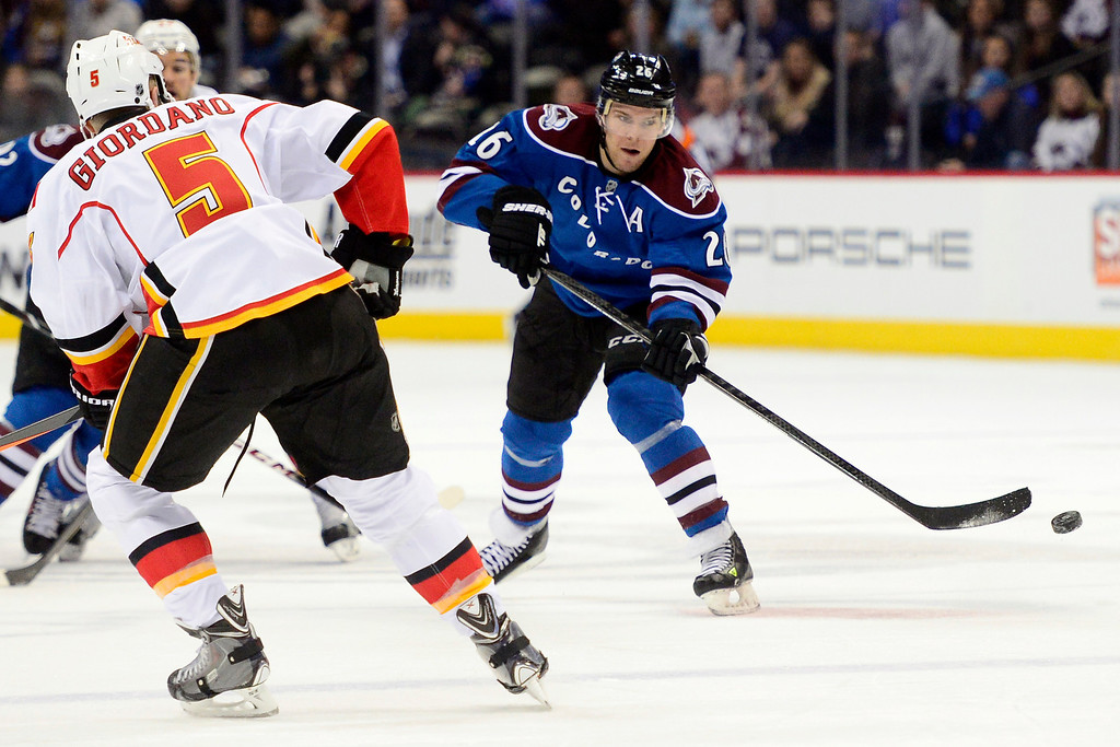 . Paul Stastny (26) of the Colorado Avalanche takes a shot as he is defended by Mark Giordano (5) of the Calgary Flames during the first period.  (Photo by AAron Ontiveroz/The Denver Post)