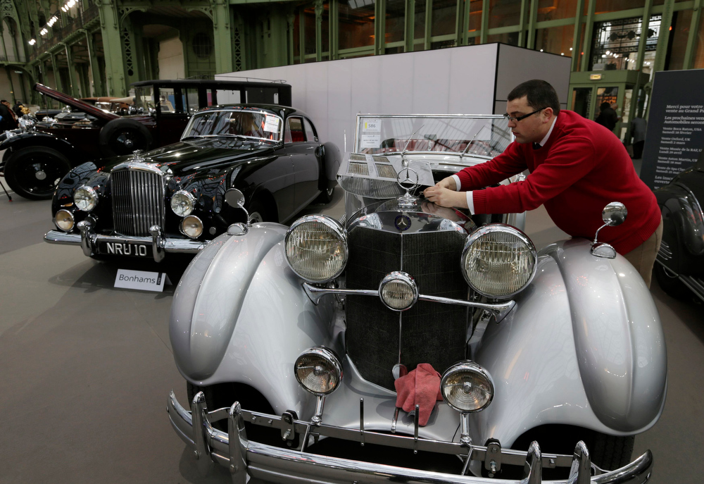 . A man cleans the Mercedes Benz 540K Cabriolet (1938) motor which is displayed during an exhibition of vintage cars and motorcycles at the Grand Palais exhibition hall as part of the Retromobile vintage car show in Paris February 6, 2013. This exceptional collection of motor cars and motorcycles will go on sale at a Bonhams\' auction on February 7.  REUTERS/Philippe Wojazer