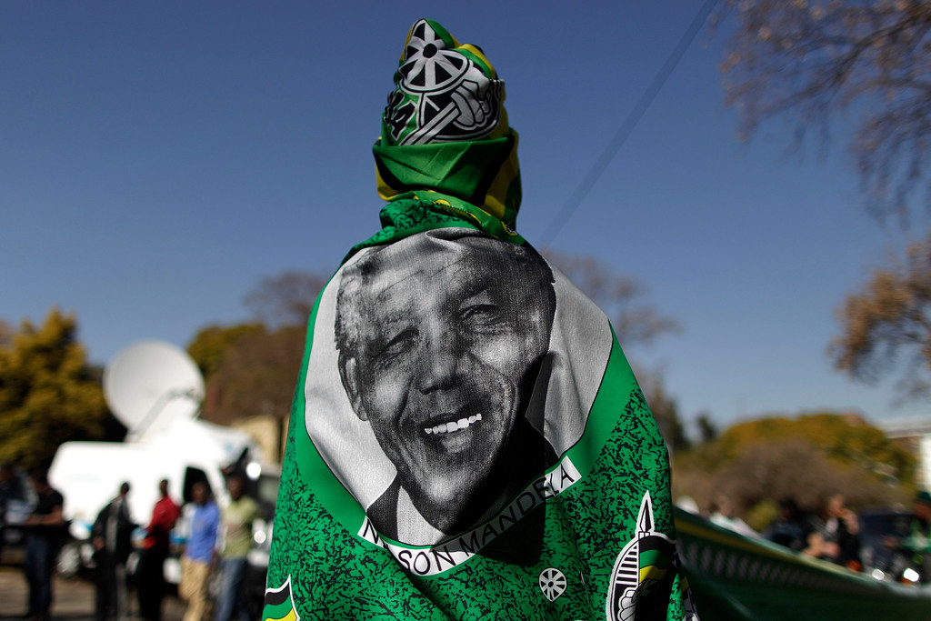 . A vendor wearing a shawl bearing the image of former South African President Nelson Mandela at the entrance to the Mediclinic Heart Hospital where Nelson Mandela is being treated in Pretoria, South Africa Friday, June 28, 2013. Members of Nelson Mandela\'s family as well as South African Cabinet ministers have visited the hospital on Friday where the 94-year-old former president is critically ill. (AP Photo/Muhammed Muheisen)