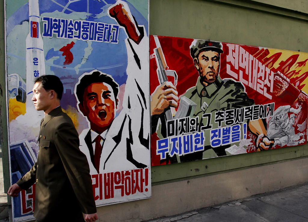 """. A North Korean man walks past propaganda posters in Pyongyang, North Korea, on Tuesday, March 26, 2013, that threaten punishment to the \""""U.S. imperialists and their allies.\"""" The U.S. recently tightened sanctions against North Korea after Pyongyang tested a nuclear device in February in defiance of international bans against atomic activity. (AP Photo/Kim Kwang Hyon)"""