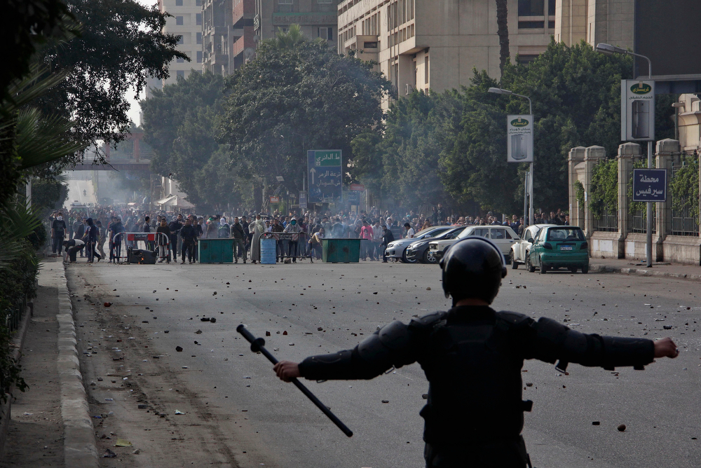 . Supporters of ousted President Mohammed Morsi, background, confront Egypt\'s security forces in Cairo, Egypt, Friday, Jan. 17, 2014. Morsi supporters held sporadic protests against this week\'s constitutional referendum as authorities said there was a deadly clash. (AP Photo/Aly Hazzaa)