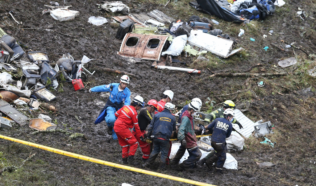 . Rescue workers recover a body from the wreckage site of an airplane crash, in La Union, a mountainous area near Medellin, Colombia, Tuesday , Nov. 29, 2016. The chartered plane was carrying a Brazilian soccer team to the biggest match of its history when it crashed into a Colombian hillside and broke into pieces, killing 75 people and leaving six survivors, Colombian officials said Tuesday. (AP Photo/Fernando Vergara)