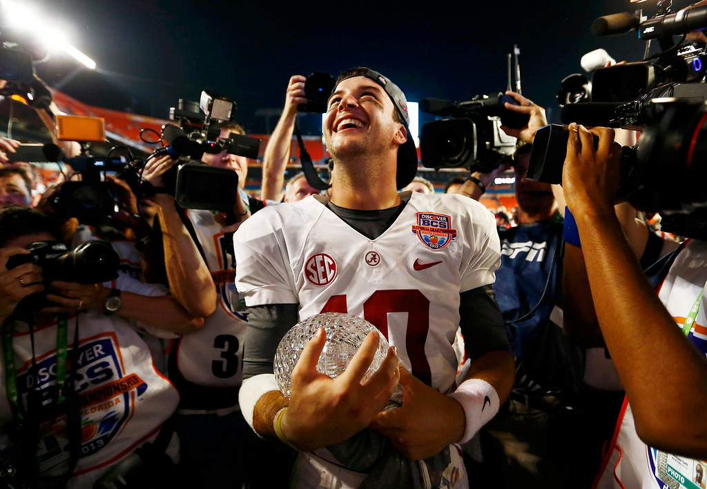. Alabama Crimson Tide quarterback AJ McCarron celebrates with the trophy after his team defeated the Notre Dame Fighting Irish in their NCAA BCS National Championship college football game in Miami, Florida, January 7, 2013.  REUTERS/Chris Keane