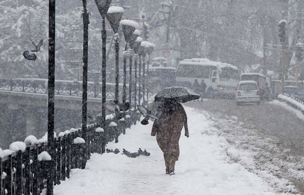 . A Kashmiri man walks as it snows in Srinagar, India, Tuesday, Dec. 31, 2013. Snowfalls in the Indian portion of Kashmir has disrupted power supply, air traffic and road traffic between Srinagar and Jammu, the summer and winter capitals of India\'s Jammu-Kashmir state, according to news reports. (AP Photo/Mukhtar Khan)