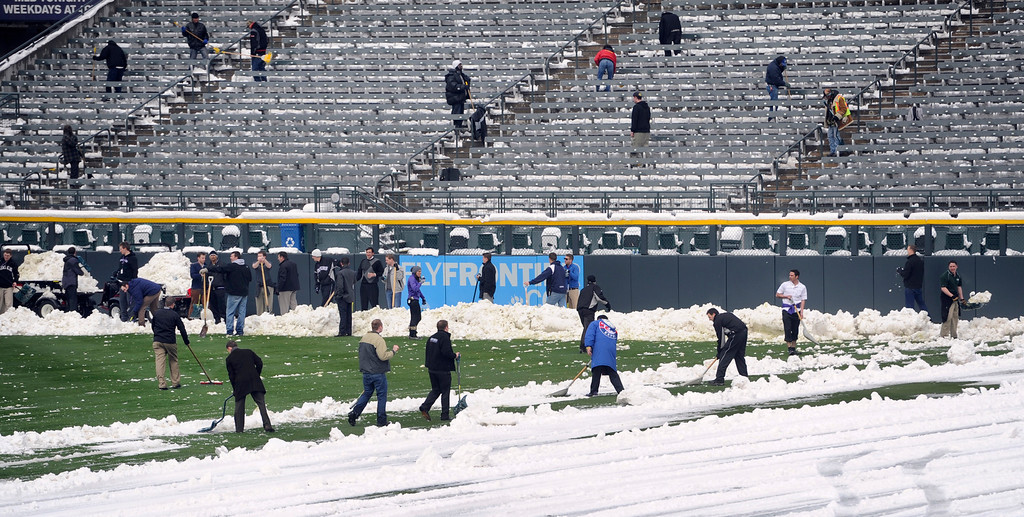 . Crews clear the snow from the seats at Coors Field after a spring snowstorm dumped close to a foot of snow downtown, canceling Monday\'s Rockies game. Weather permitting, the Rockies will play a split double header against the New York Mets  to make up for the missed game on Monday. (Photo By Kathryn Scott Osler/The Denver Post)