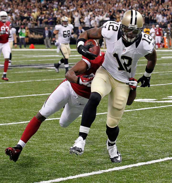 . New Orleans Saints wide receiver Marques Colston (12) is tackled by Arizona Cardinals inside linebacker Karlos Dansby after catching a pass in the first half of an NFL football game in New Orleans, Sunday, Sept. 22, 2013. (AP Photo/Bill Haber)
