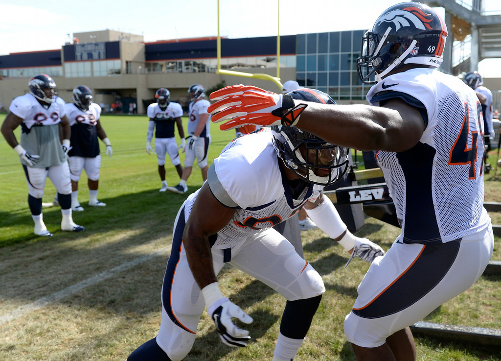 . Quanterus Smith (93) runs through drills with Chase Vaughn (49), right, on Saturday. The Denver Broncos football team hold their workouts for the team during mini-camp at Dove Valley in Centennial on Saturday, July 26, 2014. (Photo by Kathryn Scott Osler/The Denver Post)