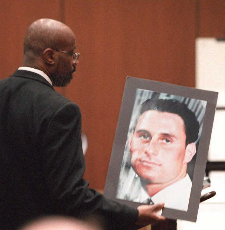 . Prosecutor Christopher Darden holds up a photograph of murder victum Ronald Goldman while he addresses the jury during closing arguments 27 September in the O.J. Simpson double murder trial in Los Angeles.  Darden put pictures of Goldman and Nicole Brown Simpson in front of the jury during his closing arguments.               (HAL GARB/AFP/Getty Images)