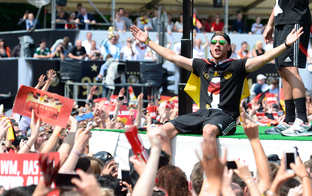 . Benedikt Hoewedes celebrates during a fan party after the arrival of the German national soccer team in Berlin Tuesday, July 15, 2014. Germany beat Argentina 1-0 on Sunday to win its fourth World Cup title.  (AP Photo/Jens Meyer)