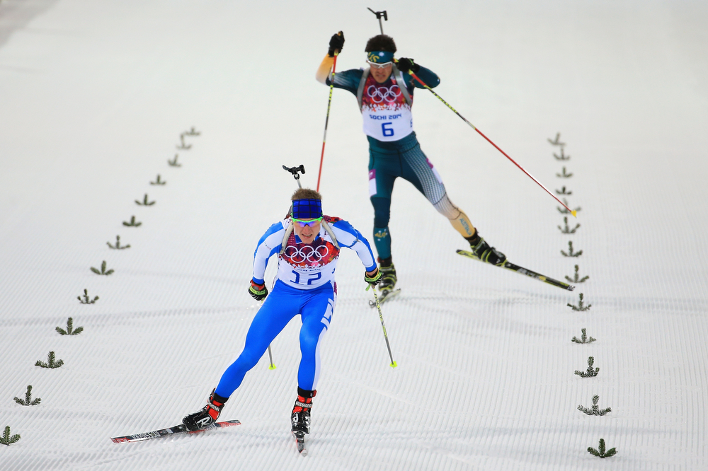 . Lukas Hofer of Italy approaches the finish line ahead of Alexei Almoukov of Australia during the Men\'s Individual 20 km during day six of the Sochi 2014 Winter Olympics at Laura Cross-country Ski & Biathlon Center on February 13, 2014 in Sochi, Russia.  (Photo by Richard Heathcote/Getty Images)