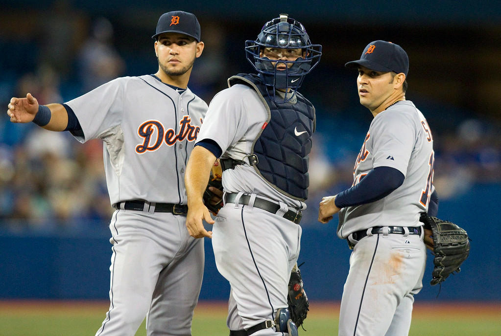 . Detroit Tigers catcher Alex Avila and Nick Castellanos signal to the trainer for pitcher Anibal Sanchez, right, during the fifth inning of a baseball game, Friday, Aug. 8, 2014 in Toronto. (AP Photo/The Canadian Press, Fred Thornhill)