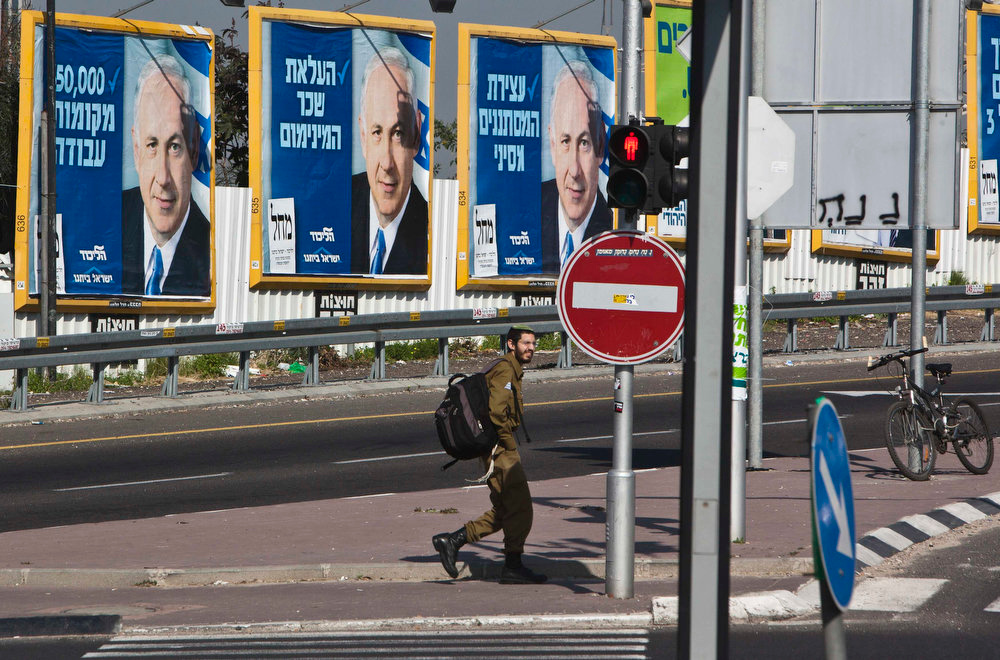 Description of . An Israeli soldier walks past campaign posters depicting Israel's Prime Minister Benjamin Netanyahu as he crosses a junction in Bnei Brak near Tel Aviv January 20, 2013. Netanyahu said on Saturday a country with as many enemies as Israel cannot afford a weak ruling party, after polls ahead of Tuesday's parliamentary election showed a slide in his support. REUTERS/Nir Elias