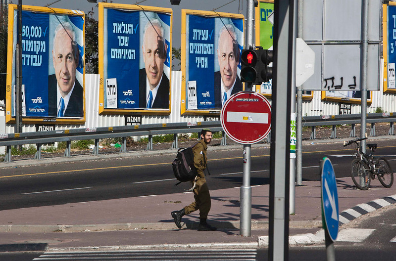 . An Israeli soldier walks past campaign posters depicting Israel\'s Prime Minister Benjamin Netanyahu as he crosses a junction in Bnei Brak near Tel Aviv January 20, 2013. Netanyahu said on Saturday a country with as many enemies as Israel cannot afford a weak ruling party, after polls ahead of Tuesday\'s parliamentary election showed a slide in his support. REUTERS/Nir Elias