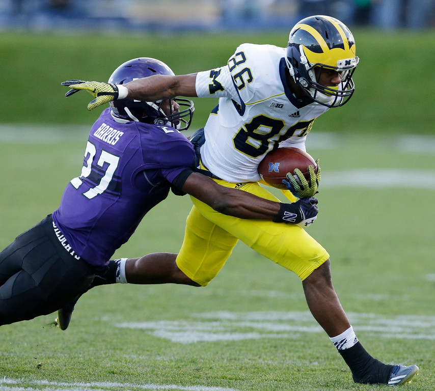. Michigan wide receiver Jehu Chesson (86) is tackled by Northwestern cornerback Matthew Harris (27) during the first half of an NCAA college football game in Evanston, Ill., Saturday, Nov. 8, 2014. (AP Photo/Nam Y. Huh)