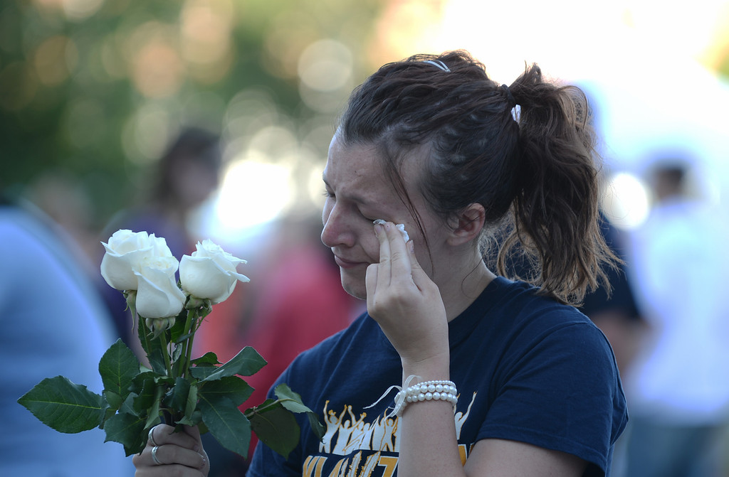 . AURORA, CO. - July 20: Chelsea Willman, 20, wipes her tears during a day of remembrance at the Aurora Municipal Center. Aurora, Colorado. July 20, 2013. People gathered outside the Aurora Municipal Center to mark the first anniversary of the deaths of 12 people and the injury of at least 70 others in a mass shooting that forever changed an entire community. (Photo By Hyoung Chang/The Denver Post)