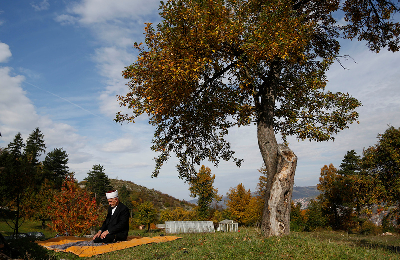 . FILE - In this Oct. 15, 2013 file photo, an elderly Bosnian Muslim prays outdoors in the outskirts of Sarajevo, Bosnia. The Great War left 14 million dead and made four empires disappear. But World War I is just one era in the history of this multicultural city. (AP Photo/Amel Emric, File)