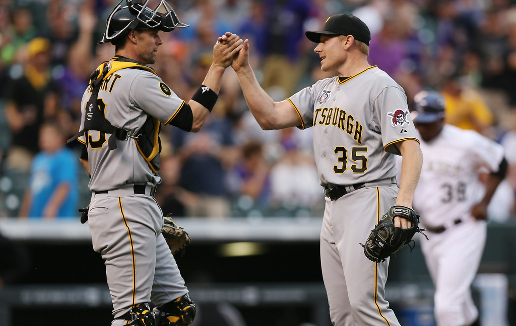 . Pittsburgh Pirates catcher Chris Stewart, left, congratulates relief pitcher Mark Melancon after Melancon retired the Colorado Rockies with nine pitches in the ninth inning of the Pirates\' 7-5 victory in a baseball game in Denver, Sunday, July 27, 2014. (AP Photo/David Zalubowski)