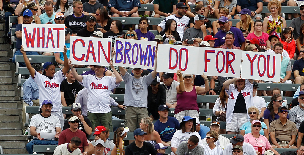. Philadelphia Phillies fans hold up pieces of a sign in support of Phillies left fielder Domonic Brown as he takes his position to face the Colorado Rockies in the first inning of a baseball game in Denver on Sunday, June 16, 2013. (AP Photo/David Zalubowski)