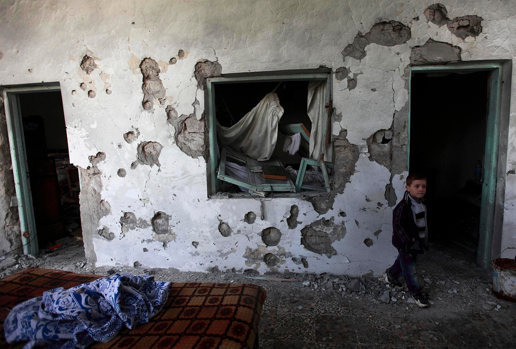 . A child walks in a house damaged after heavy shelling by government forces in Sermeen near the northern city of Idlib February 28, 2012. REUTERS/Zohra Bensemra
