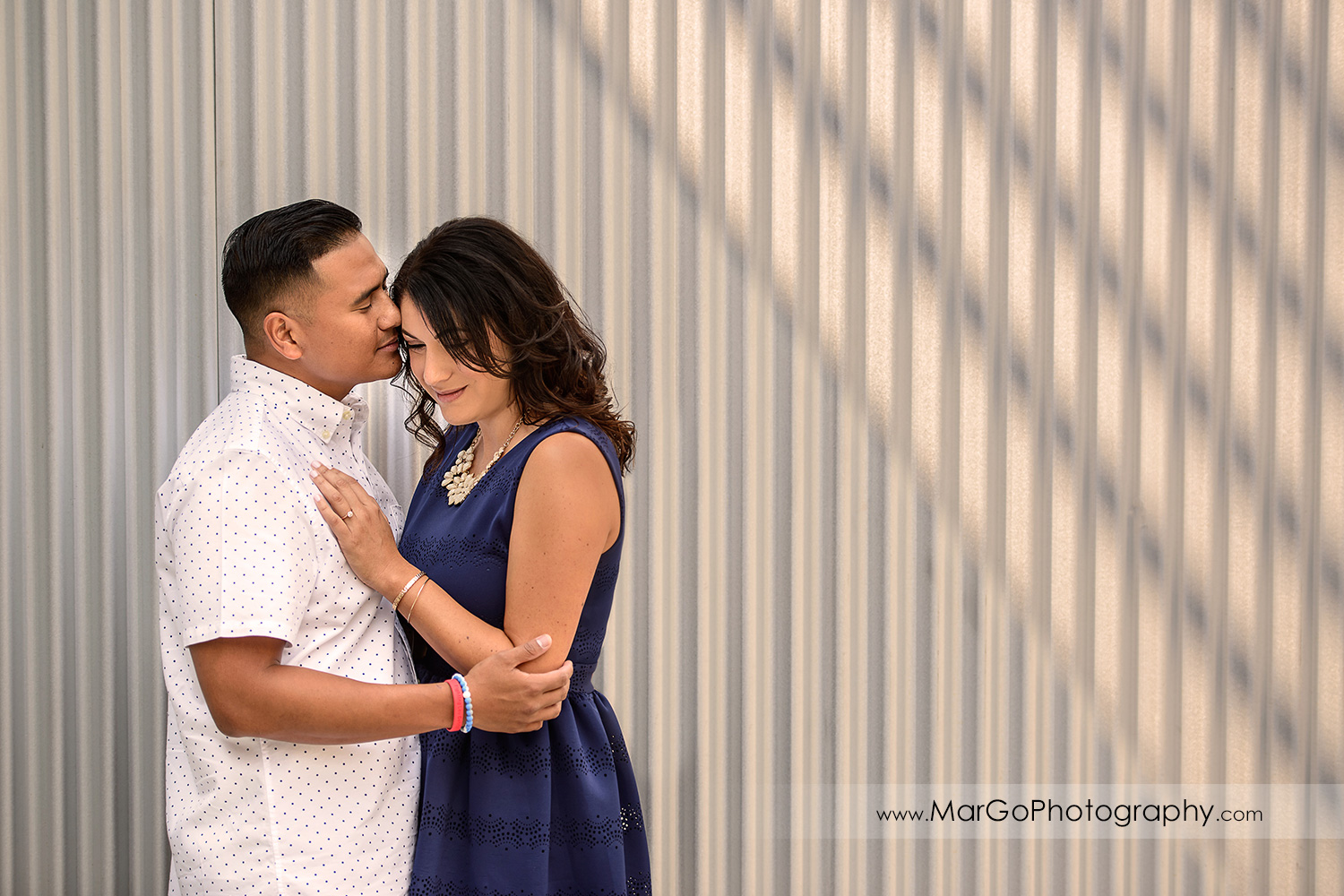 romantic portrait of woman in blue dress and man in white shirt standing standing in front of metal wall during engagement session at San Pedro Square Market in San Jose