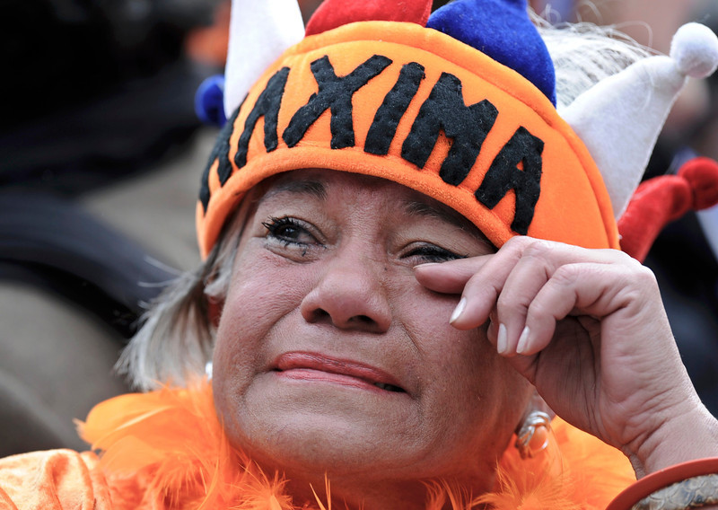 . A woman cries as the new Dutch King Willem-Alexander succeeds his mother Queen Beatrix of Netherlands outside the Royal Palace in Amsterdam April 30, 2013. The Netherlands is celebrating Queen\'s Day on Tuesday, which will also mark the abdication of Queen Beatrix and the investiture of her eldest son Willem-Alexander.               REUTERS/Paul Vreeker