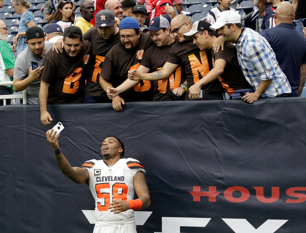 . Cleveland Browns linebacker Christian Kirksey (58) takes a photo with a smart phone of himself and fans after their NFL football game against the Houston Texans on Sunday, Oct. 15, 2017, in Houston. (AP Photo/Eric Gay)