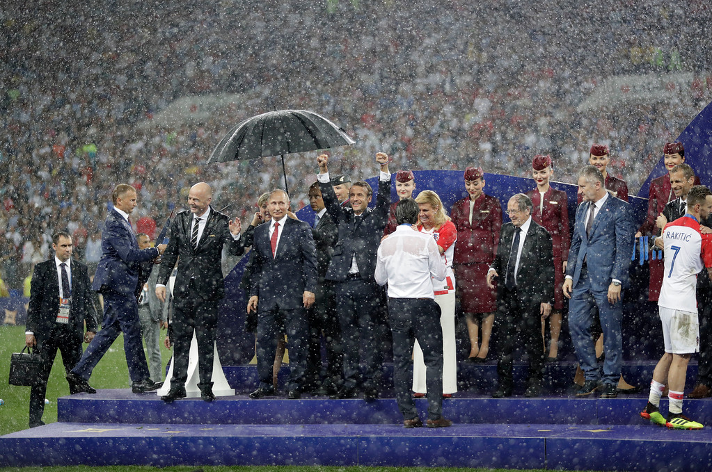 . FIFA President Gianni Infantino, third left, gestures as Russian President Vladimir Putin stands underneath an umbrella next to French President Emmanuel Macron as Croatian President Kolinda Grabar-Kitarovic greets Croatia head coach Zlatko Dalic after the final match between France and Croatia at the 2018 soccer World Cup in the Luzhniki Stadium in Moscow, Russia, Sunday, July 15, 2018. France won the final 4-2. (AP Photo/Matthias Schrader)