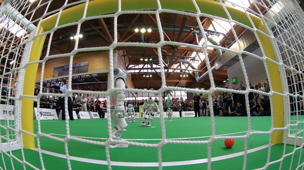 ". Robots of the team ""Robo Eireann\"" play the ball during \""Standard Plattform Liga\"" match at  the \""RoboCup German Open 2013\"" in Magdeburg, eastern Germany on April 26, 2013. The 4th edition of RoboCup German Open 2013 takes place from April 26-28 and is attended by 43 international RoboCup Major League teams from 14 countries demonstrating the state-of-the-art robotics in soccer, rescue and service robots. JENS WOLF/AFP/Getty Images"