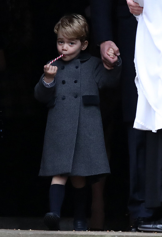 . Prince George eats a sweet as he leaves following the morning Christmas Day service at St Mark\'s Church in Englefield, England, on Sunday Dec. 25, 2016. A heavy cold is keeping Queen Elizabeth II from attending the traditional Christmas morning church service near her Sandringham estate in rural Norfolk, England. (Andrew Matthews/Pool via AP)
