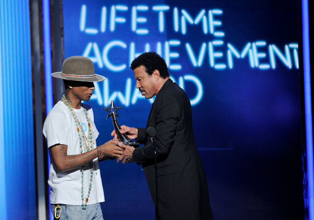 . Pharrell Williams, left, presents the lifetime achievement award to Lionel Richie at the BET Awards at the Nokia Theatre on Sunday, June 29, 2014, in Los Angeles. (Photo by Chris Pizzello/Invision/AP)