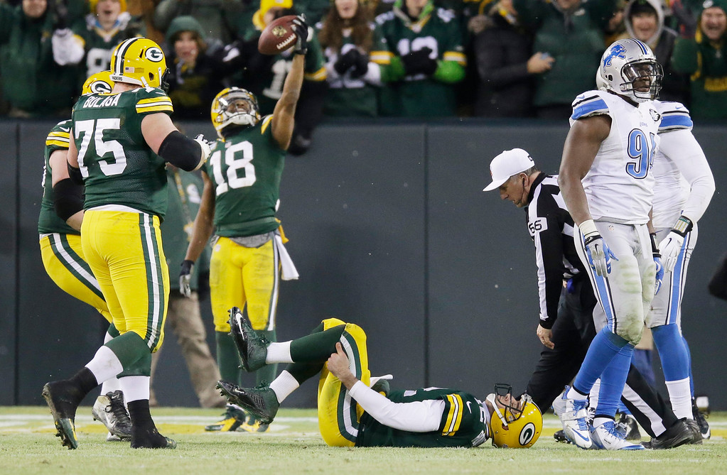 . Green Bay Packers\' Aaron Rodgers (12) holds his leg as Randall Cobb (18) celebrates his touchdown catch during the first half of an NFL football game against the Detroit Lions Sunday, Dec. 28, 2014, in Green Bay, Wis. Rodgers left the game on a cart. (AP Photo/Tom Lynn)