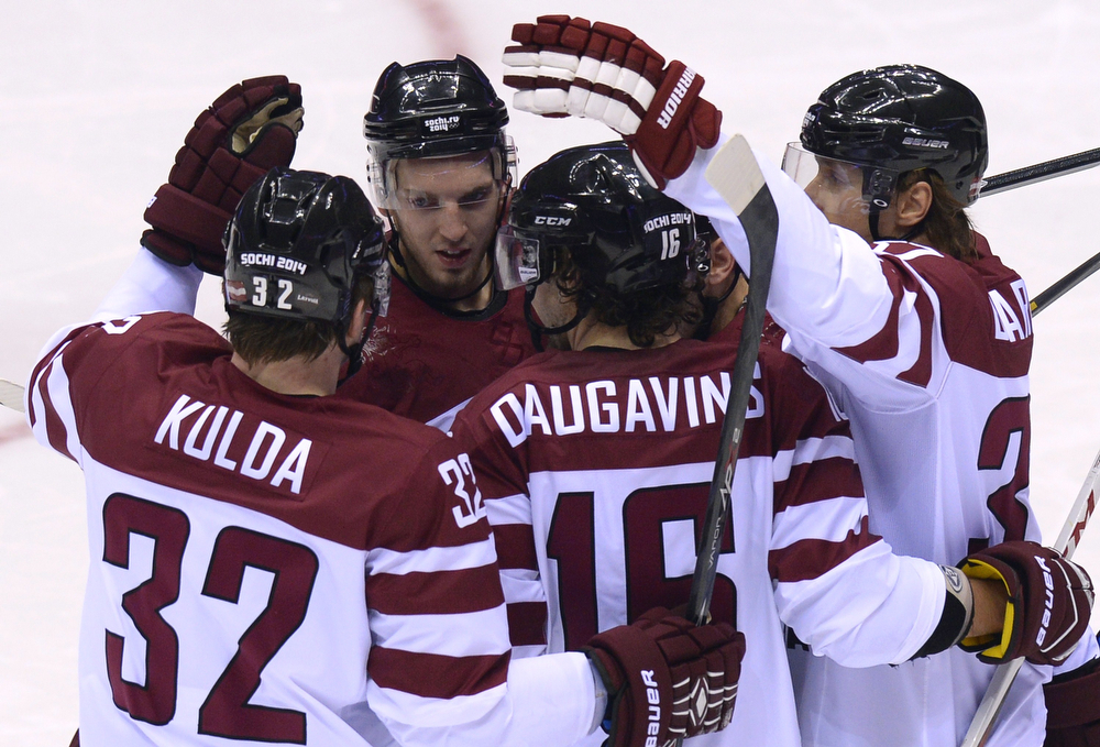 . Latvia\'s players celebrate scoring during the Men\'s Ice Hockey Play-offs Switzerland vs Latvia at the Bolshoy Ice Dome during the Sochi Winter Olympics on February 18, 2014.  (ALEXANDER NEMENOV/AFP/Getty Images)