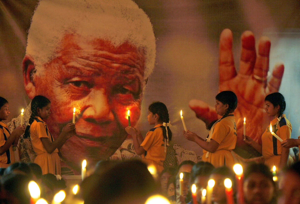 . Schoolchildren hold candles near a giant portrait of former South African President Nelson Mandela in Chennai, India, Friday, Dec. 6, 2013.  Mandela, who died Dec. 5 at age 95, was considered a master of forgiveness. He became South Africaís first black president after spending nearly a third of his life as a prisoner of apartheid. (AP Photo/Arun Sankar K)