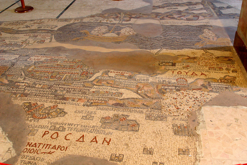Madaba - St George's Church mosaic map - This part of the map shows the Dead Sea (with boats crossing it).  The Jordan River is flowing into the Dead Sea from the left (left is north, top is east).  Below that is a mini map of Jerusalem depicting city walls, gates and the central road (cardo).