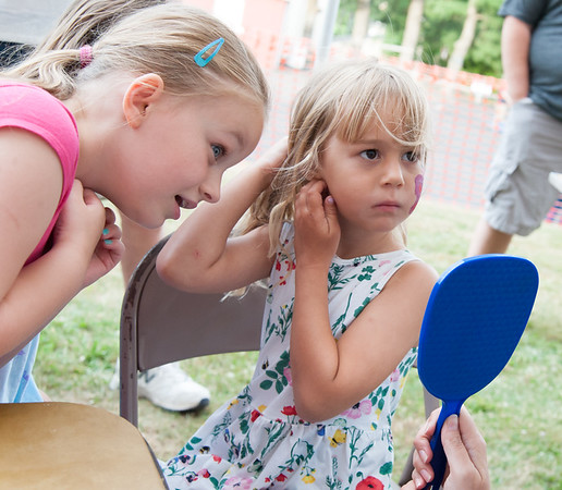 06/21/18 Wesley Bunnell | Staff Zosia Jarzabek , age 4, looks at face painter Michelle Szylobryt after having a butterfly painted on her face on the first night of the Sacred Heart Parish Festival on Friday evening as Krystan Nadeau, age 6, looks on.